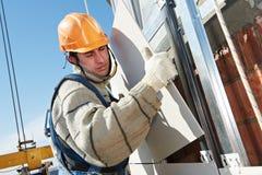 Budowniczy przy wietrzącą fasady płytki instalacją Fotografia Stock