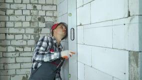 Budowniczy sprawdza płaszczyznowość marża wykłada na blok ścianie z bąbla poziomem zbiory wideo