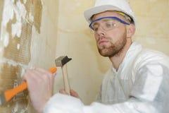 Budowniczy używa młot usuwać ściana tynk obraz stock