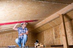 Budowniczy Używa poziom na suficie w Niedokończonym domu Obrazy Royalty Free