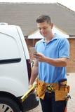 Budowniczy Z Van Checking wiadomościami tekstowymi Na telefonie komórkowym Outside Obrazy Stock