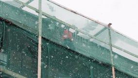 Budowniczych pracowników stojak na budowy rusztowaniu i rzutu śnieg od dachu zbiory wideo