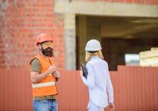 Budowy bezpieczeństwa inspekcja Dyskutuje postępu projekt Kobieta inspektor i brodaty brutalny budowniczy dyskutujemy zdjęcie royalty free
