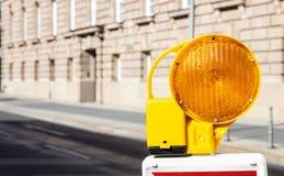 Budowy bezpieczeństwo Uliczna barykada z ostrzegawczą sygnałową lampą na drodze, plama budynku tło obraz royalty free