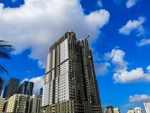Budowy, dźwigowego i dużego budynek w budowie przeciw błękitnemu chmurnemu niebu, obrazy royalty free