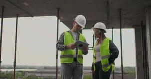 Budowy drużyna, architekt, budowniczy lub pracownik z hełmami dyskutujemy na szafot budowy planie lub zbiory wideo