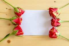 The buds of roses lie on the edges of a sheet of paper on a wood Stock Photos