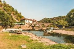 Budva Montenegro - Augusti 26, 2017: Den gamla välvda stenbron av den Crnojevica floden på Montenegro Royaltyfri Foto