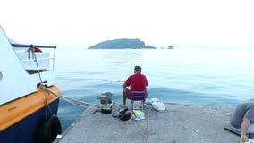 Budva, Montenegro - 27 de junho de 2017 Fishermans que senta-se no cais e que pesca no mar de adriático Do zumbido vista panorâmi video estoque
