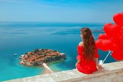 Budva, Montenegro Hintere Ansicht des Mädchens im roten Kleid über Sveti Suite Stockfotografie