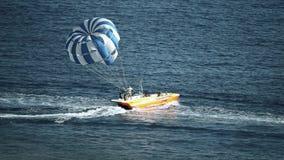 BUDVA MONTENEGRO - JULI 26, 2018 Parasailing hoppa fallskärm och snabba motorbåten på havet lager videofilmer