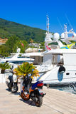 BUDVA, MONTENEGRO - JULY 12, 2015: Motobike in sea port with many tourist boats and luxury yachts in the small shipyard Stock Photography