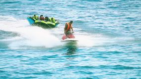 Budva, Montenegro - July 26, 2018. People have fun riding inflatable raft towed by jet ski, slow motion shot stock video