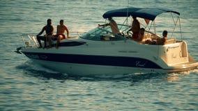 Budva, Montenegro - July 26, 2018. People riding Bayliner motorboat at sea at sunset, slow motion shot stock video