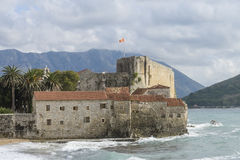 Budva, Montenegro - October 21 2016: national flag of Montenegro. Flying high above old citadel walls while a storm surge is hitting against the citadel walls stock photography