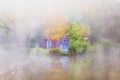 Budy obok małego stawu na mgłowym dniu Fotografia Royalty Free