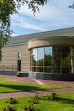 Budynek kurenda foyer z odzwierciedlającymi okno i gazonem z zieloną trawą przed nim obrazy royalty free