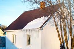 Budynek mieszkalny śnieg na dachu w słońcu na zima dniu, troszkę, horyzontalny strzał zdjęcie stock
