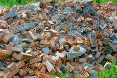 Budynków gruzy od łamanych cegieł i płytek w trawie Obrazy Stock