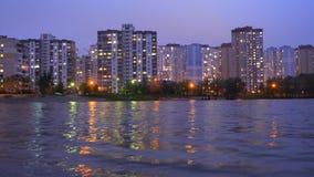 Budynki mieszkaniowi lokalizować blisko jeziora, podczas zmierzchu z purpurowym niebem odbija w wodzie Wiecz?r pejza? miejski zbiory