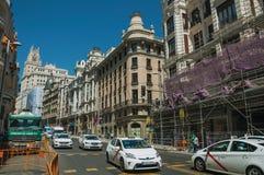 Budynki na ruchliwej ulicie z ludźmi i samochodami w Madryt obrazy royalty free