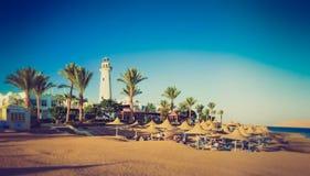 Budynki palmy aleja na egipcjanin plaży i luksusowy hotel, latarnia morska morza czerwonego Egipt Fotografia Stock