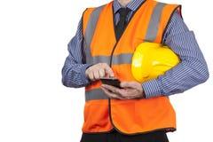 Budynku geodeta w pomarańczowej widoczności kamizelce używać jego smartphone Obraz Royalty Free