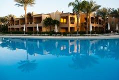 Budynku odbicie na pływackiego basenu wodzie Wieczór słońce na budynku z dwa palmami odbija nawadniać lustro obraz royalty free