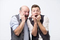 Budzący emocje odurzeni mężczyźni gapią się przy kamerą z bugged oczami strach pełno, utrzymanie ręk blisko otwierający mouthes zdjęcie stock