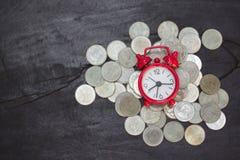 Budzik i monety na drewnianym stole, pieniędzy oszczędzania, inwestycja, narastający pojęcie, sztaplowania dorośnięcia monety, Ra obrazy royalty free