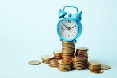 Budzik i złote pieniądze monety, kapitalizacja Czas jest pieniądze pojęciem, zapłata fotografia stock