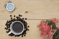 Budzik, kawa i kwiaty na drewno stole, Fotografia Stock