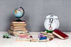 Budzik, książki, zabawki i kula ziemska na szarym tle, Fotografia Stock