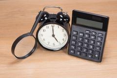 Budzik między magnifier i kalkulatorem zdjęcie stock