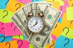 budzik na tle znak zapytania, USA dolary pojęcie przychodu pieniądze, pomysły dla pensji i strata czas a, zdjęcie stock