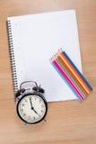 Budzik z barwionymi ołówkami kłama na notatniku obrazy stock