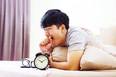 Budzik z mężczyzna na łóżku Zdjęcie Stock