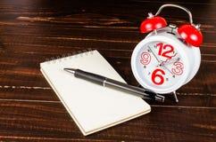 Budzik z notatnikiem i czarnym piórem Zdjęcia Royalty Free