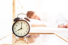 Budzik z sypialną dziewczyną w łóżkowym pokoju Gnuśny czas w wakacje fotografia stock