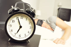 Budzika i młodego człowieka dosypianie w łóżku z sen maską Obrazy Stock
