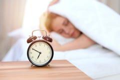 Budzika opposite śpiąca młoda kobieta Wcześnie budził się, dostawać dosyć sen pojęcia obrazy stock