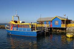 Bue lumineux et bateau jaune contre un bâtiment bleu et jaune Photos libres de droits
