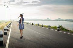 Bueatifulmeisje in kleding op de weg dichtbij dam Stock Afbeeldingen