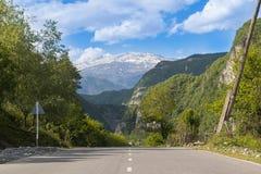 Buen camino en el fondo de montañas nevosas foto de archivo libre de regalías