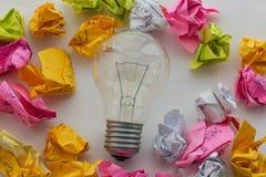Buen concepto de la idea con el papel y la bombilla coloridos arrugados Foto de archivo