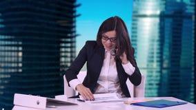 Buen reparto La mujer de negocios joven sonriente feliz en un traje de negocios muestra el pulgar en la cámara Ella se sienta en  almacen de video
