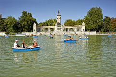 Buen Retiro Park, Madrid, Spain. MADRID - JULY 29: The Monument to Alfonso XII, Tourists boating in a lake people enjoy summer evening in Buen Retiro Park on Royalty Free Stock Photography