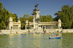 Buen Retiro Park, Madrid, Spain. MADRID - JULY 29: The Monument to Alfonso XII, Tourists boating in a lake people enjoy summer evening in Buen Retiro Park on Stock Images