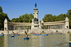 Buen Retiro Park, Madrid, Spain. MADRID - JULY 29: The Monument to Alfonso XII, Tourists boating in a lake people enjoy summer evening in Buen Retiro Park on Stock Photo