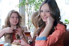 Buen tiempo y amigos de muchacha felices en un restaurante Imagenes de archivo